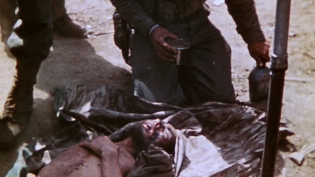 marine corpsmen preparing casualty for evacuation setting him on shelter half wrapping it over him and giving him a drink of water / iwo jima japan - schlacht um iwojima stock-videos und b-roll-filmmaterial