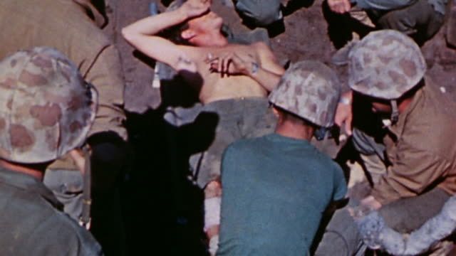 marine corpsmen tending casualties on stretchers / iwo jima japan - schlacht um iwojima stock-videos und b-roll-filmmaterial