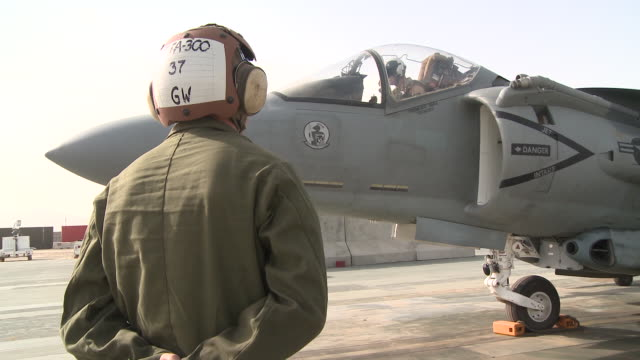 A U.S. Marine ground crew member communicates with an AV-8B Harrier pilot.