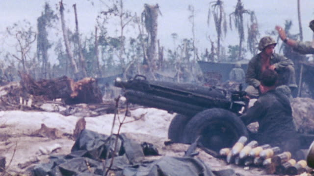 vídeos de stock e filmes b-roll de marine gun crew loading and firing 75mm pack howitzer in pacific warfare during world war ii - fuzileiro naval