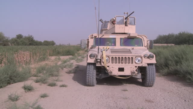 A U.S. Marine gunner mans a Humvee turret as riflemen move forward on a dirt road.