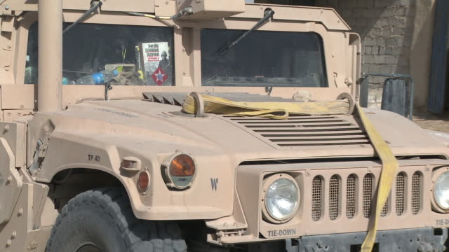 stockvideo's en b-roll-footage met a u.s. marine holds a book up to the window of a humvee as a convoy passes stone buildings along a gravel road. - humvee