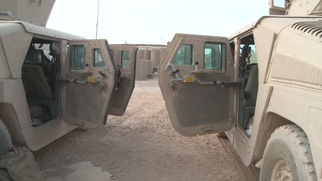 U.S. Marine Humvees have open doors in a logistics area.
