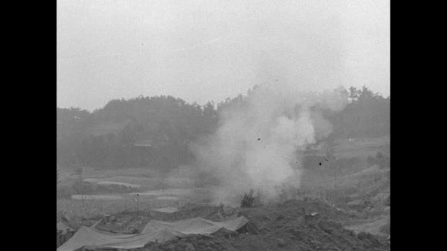 US Marine in foxhole pan to battlefield with explosion / montage artillery fires explosion on hill soldiers with jeep antiaircraft gun muzzle...