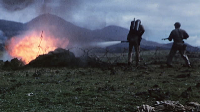 S Marine in prone firing position holding his helmet as other Marines use flamethrowers grenades and fire extinguishers to burn out buried enemy...