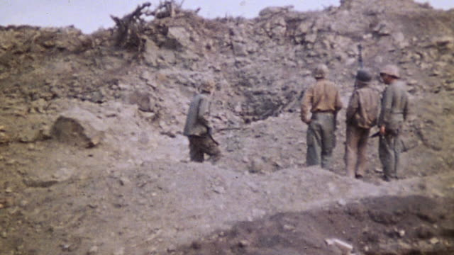 marine infantry advancing along rocky ridge and checking cave mouth / iwo jima japan - schlacht um iwojima stock-videos und b-roll-filmmaterial