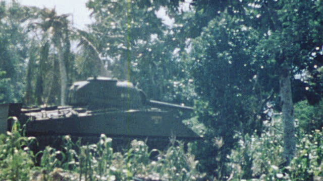 S Marine infantry advancing through the jungle under cover of M4 Sherman tank / Saipan Mariana Islands