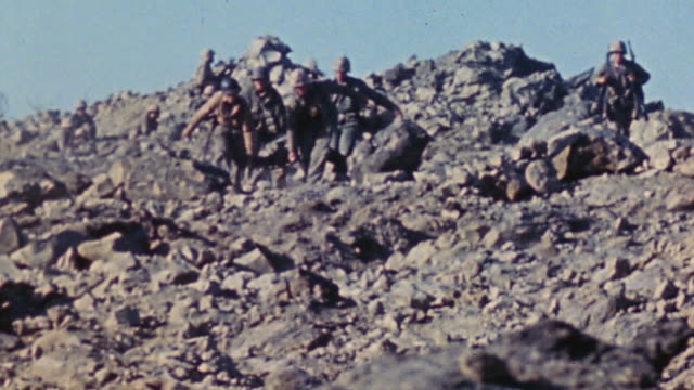 marine infantry crossing rocky ridge at a run and medics descending slope with casualty on stretcher / iwo jima japan - battle of iwo jima stock videos and b-roll footage
