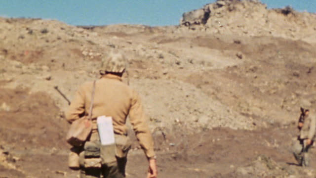 marine infantry crossing rough rocky terrain below ridge and climbing to cross it / iwo jima japan - schlacht um iwojima stock-videos und b-roll-filmmaterial