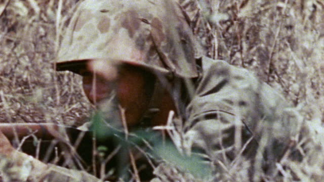 marine infantry prone in tall grass and aiming m1 rifles / saipan, mariana islands - rifle stock videos & royalty-free footage