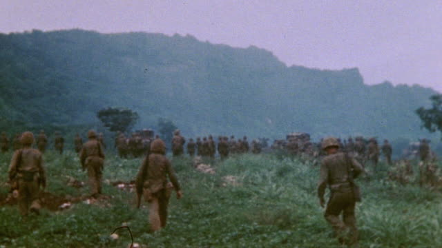Marine infantry supported by M4 Sherman tank advancing into heavy underbrush during World War II