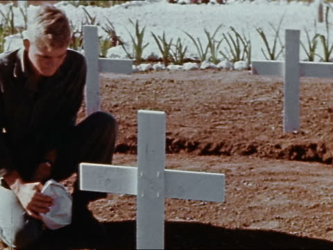 Marine kneeling at grave in cemetery with white crosses / Philippines