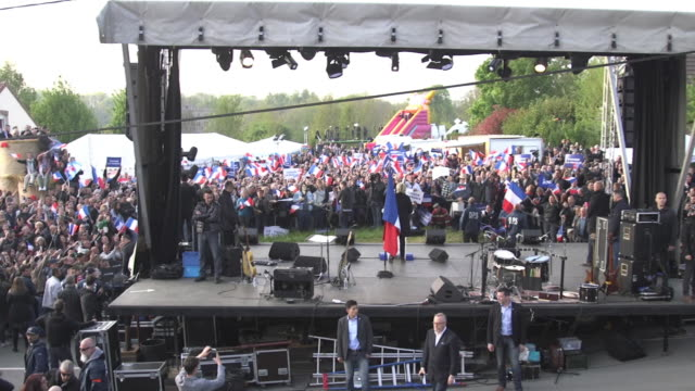 marine le pen walks to the stage then speaks on stage while campaigning in ennemain france with thousands of onlookers holding french flags and... - national front stock videos & royalty-free footage