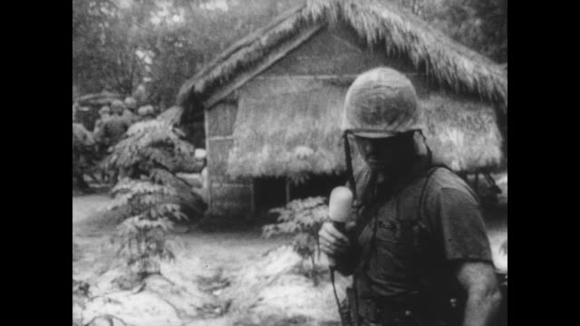 marine lieutenant dick nicklin holds microphone and records a statement in the wake of a search and clear mission during the vietnam war / nicklin... - indocina video stock e b–roll