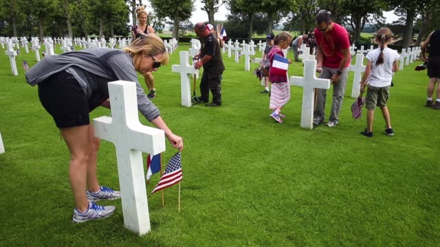 vidéos et rushes de us marine mark weinrich his wife kathryn and their daughters charlie and emily help plant us and french flags at the graves of us soldiers most of... - cimetière
