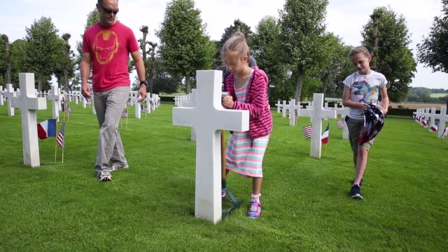 US Marine Mark Weinrich his wife Kathryn and their daughters Charlie and Emily help plant US and French flags at the graves of US soldiers most of...
