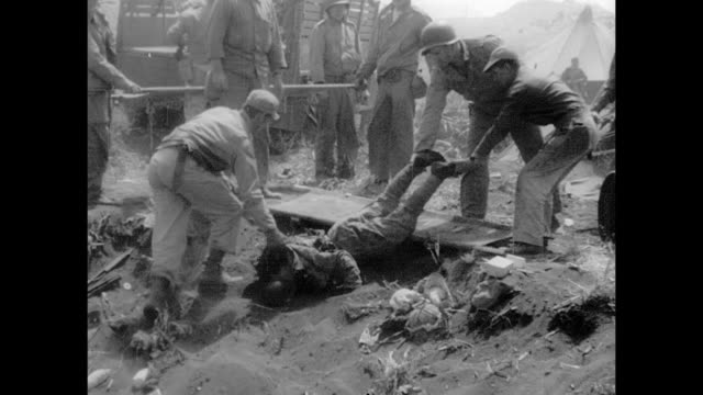 marine pulling out machine gun from rubble dead japanese soldier on beach us soldiers pulling carrying dead japanese men on stretchers onto back of... - schlacht um iwojima stock-videos und b-roll-filmmaterial