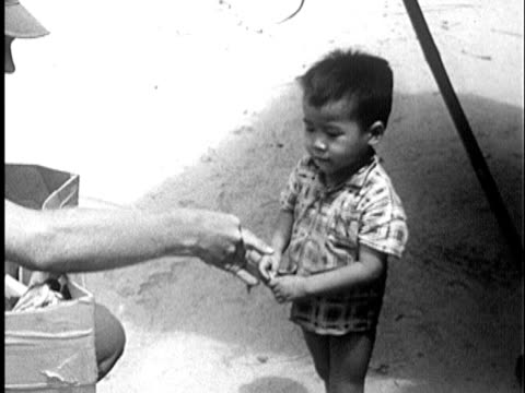 S Marine putting food in hand of young Vietnamese boy / Vietnam / AUDIO