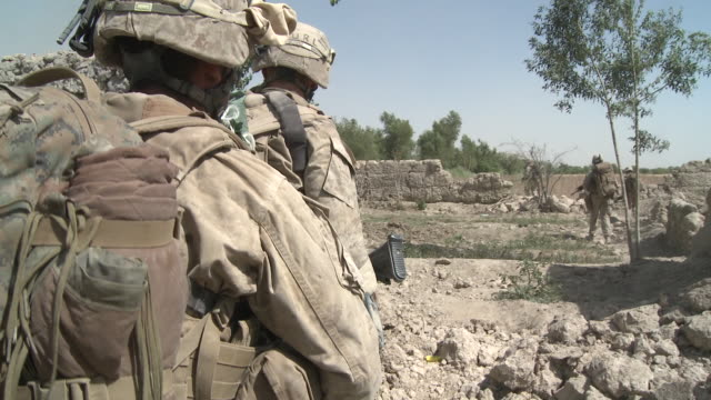 A U.S. Marine rifle squad walks through debris and past shattered walls.