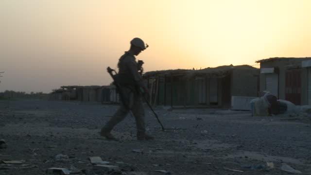 a u.s. marine rifleman kneels as a combat engineer sweeps for ieds. - provinz helmand stock-videos und b-roll-filmmaterial