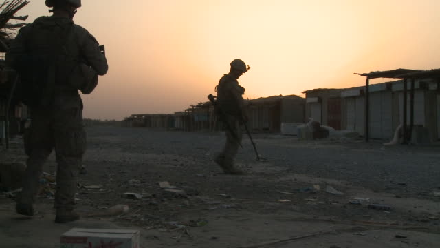 a u.s. marine rifleman provides security as a combat engineer sweeps a marketplace for ieds. - provinz helmand stock-videos und b-roll-filmmaterial