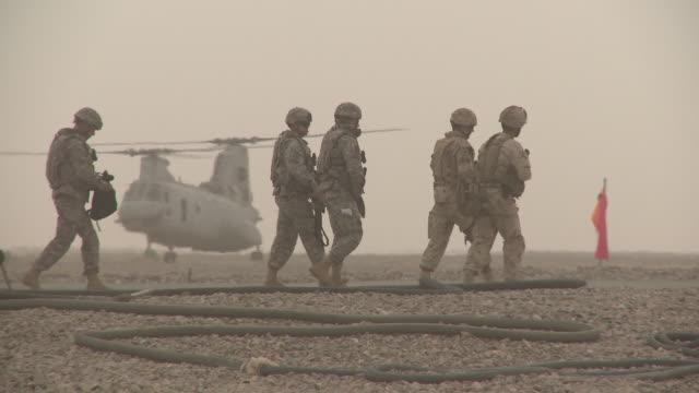 U.S. Marine riflemen walk away off a dusty landing area.