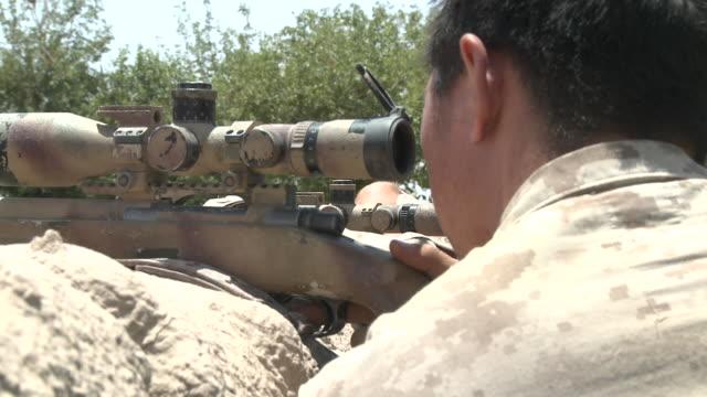 A U.S. Marine scout-sniper sights in his M40A3 sniper rifle.