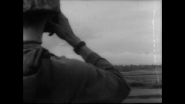 us marine skyhawk jets fly above rice paddy in vietnam / bombs drop napalm as soldiers on ground watch / clouds of black smoke rise out of the... - strohhut stock-videos und b-roll-filmmaterial