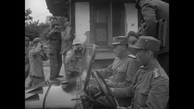 US Marine smoking cigarette talking with South Korean soldiers / North Korean and Chinese delegates walking from building / MS General Nam Il walking...