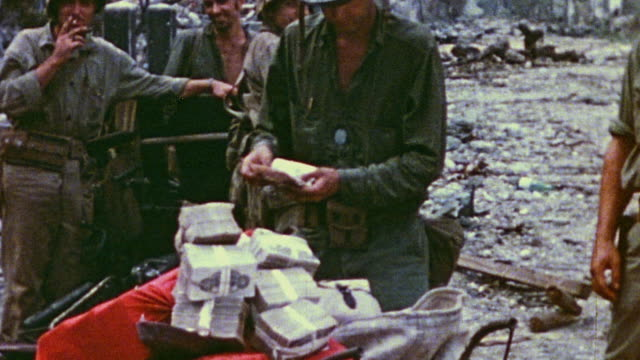 s marine standing in shelled village removed bundled paper currency from a sack and returning the bundles to the sack with fellow soldiers observing... - financial accessory stock videos & royalty-free footage