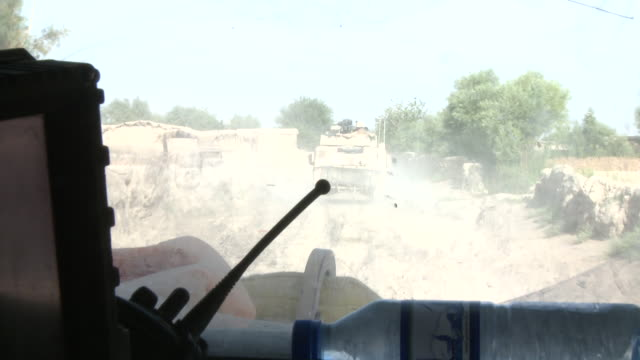 a u.s. marine truck driver follows convoy vehicles as an afghan girl watches. - convoy stock videos and b-roll footage