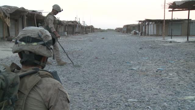 vídeos de stock, filmes e b-roll de a u.s. marine uses a mine detector to sweep a dirt street. - helmand