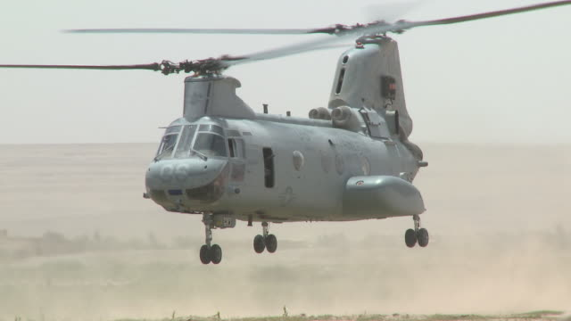 A U.S. Marine watches as a CH-46 takes off.