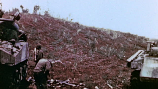 marines and line of parked tanks below crest of ridge shells stacked nearby / saipan mariana islands - mariana islands stock videos and b-roll footage