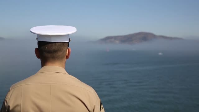 marines and sailors assigned to uss america man the rails as the ship pulls into port for fleet week san francisco oct 6 2014 during fleet week... - 海軍点の映像素材/bロール