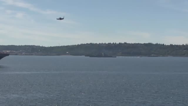 US Marines and sailors observe ships passing by during Marine Week Seattle July 30 2014 Marine Week Seattle showcases Marine Corps equipment aircraft...