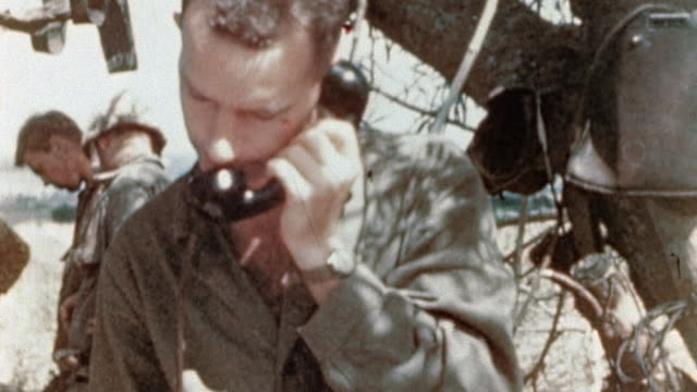 vídeos de stock, filmes e b-roll de s marines at field communications post soldier working in a tree soldiers using field telephone and coordinates map during wwii pacific campaign /... - enfoque de objeto sobre a mesa