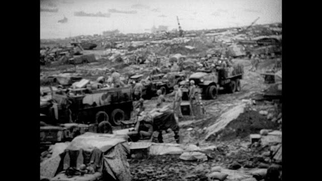 us marines base on iwo jima beach w/ scattered equipment vehicles / vs us soldiers by tents getting cleaned rinsing feet spreading shaving cream... - battle of iwo jima stock videos & royalty-free footage
