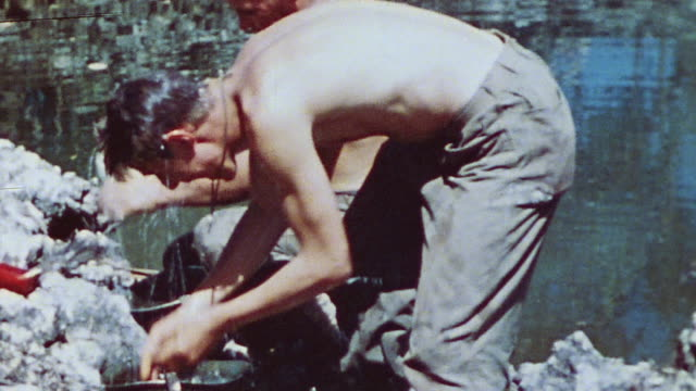 s marines bathing at water's edge sitting reading and cleaning weapons during world war ii / iwo jima japan - battle of iwo jima stock videos and b-roll footage