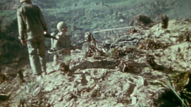 marines blasting a flamethrower through a cave mouth and japanese prisoner of war in shorts acting as interpreter to persuade the soldiers inside to... - pacific war video stock e b–roll