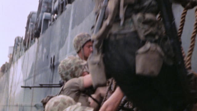 marines boarding an lst from higgins boat by climbing cargo net - pacific war stock videos & royalty-free footage