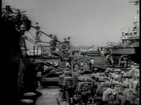 Marines boarding transport ship on dock LA WS Workers loading fighter airplanes onto carrier LA MS Crane loading tank WS Dock cranes loading cargo MS...