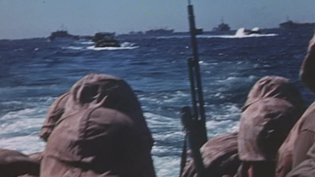 marines bobbing up and down in dukw heading toward shore other amphibious landing craft in their wake during world war ii pacific island invasion - 硫黄島点の映像素材/bロール
