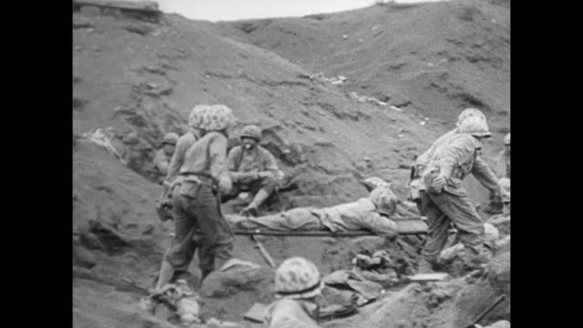 marines carrying injured on stretcher across sand hills on beach of iwo jima soldiers in defensive positions on beach radioman on large walkie talkie... - battle of iwo jima stock videos & royalty-free footage