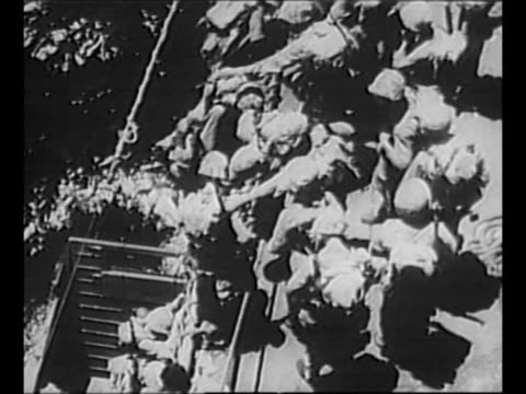us marines climb over side of ship enter landing craft / montage landing barges move in water as marines approach saipan during world war ii / ws... - landing craft stock videos & royalty-free footage