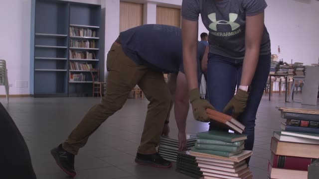 us marines conduct a community relations project with italian citizens in moving books and furniture in a building that was damaged during an... - e book stock videos & royalty-free footage