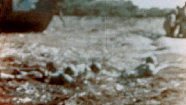 s marines crawling on their bellies on the beach with lvt beyond and soldiers on foot along with jeep advancing forward during wwii pacific campaign... - mariana islands stock videos and b-roll footage