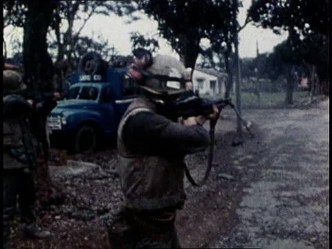 marines crouching in street firing machine guns / marines standing in street firing m16s / marines entering a house, m16s in hands - 海兵隊員点の映像素材/bロール