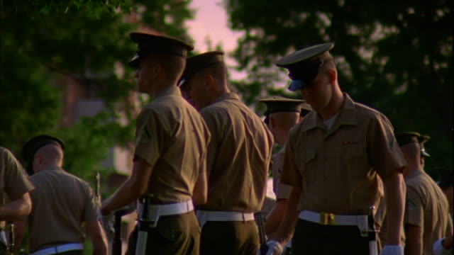 Marines dressed in short sleeve service uniforms and gloves at ease standing in group near United States Marine Corps War Memorial statue Military...