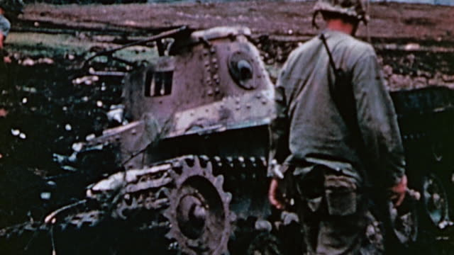 marines examining burned and wrecked japanese tankettes on battlefield with casualty nearby / saipan mariana islands - 荒廃した点の映像素材/bロール